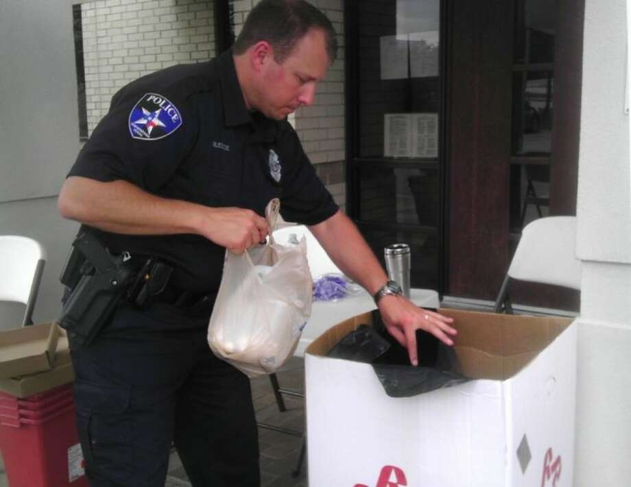 Officer Mike Bledsoe of Shenandoah Police Department empties a bag of unused prescription drugs into a trash bag during a citywide drug take-back event on Saturday.