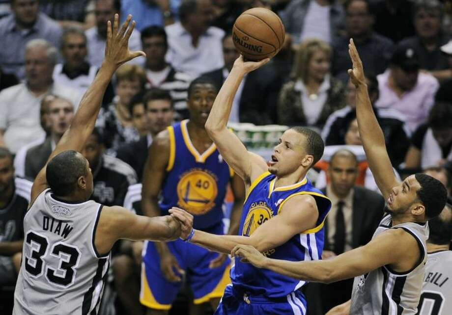 Golden State Warriors point guard Stephen Curry shoots between San Antonio Spurs center Boris Diaw and point guard Cory Joseph during the second half of Game 1 on Monday in San Antonio. Photo: Darren Abate