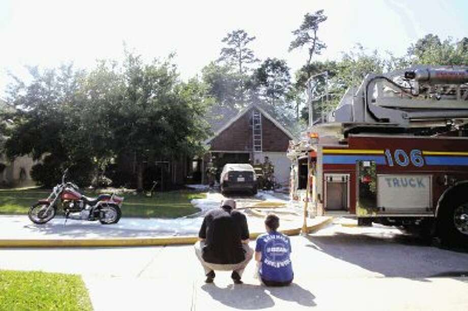 Homeowners watch as emergency personnel from The Woodlands and Needham responded to a fire at their house on Tuesday in Harpers Landing. / Conroe Courier