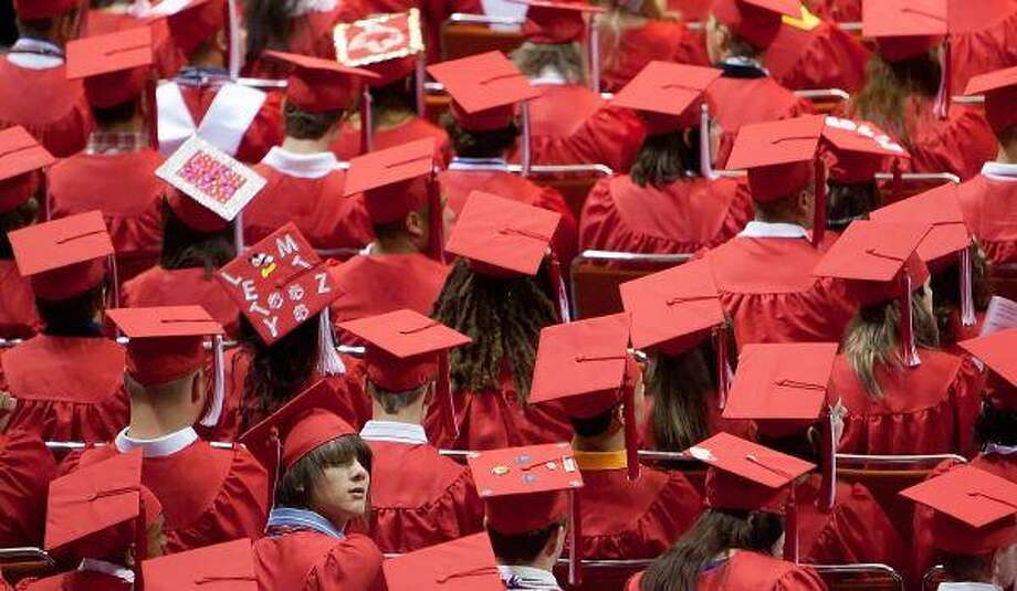 TOP: From a sea of red, a Splendora High School graduate looks up into the crowd during the commencement ceremony Friday at Sam Houston State University in Huntsville. / The Courier