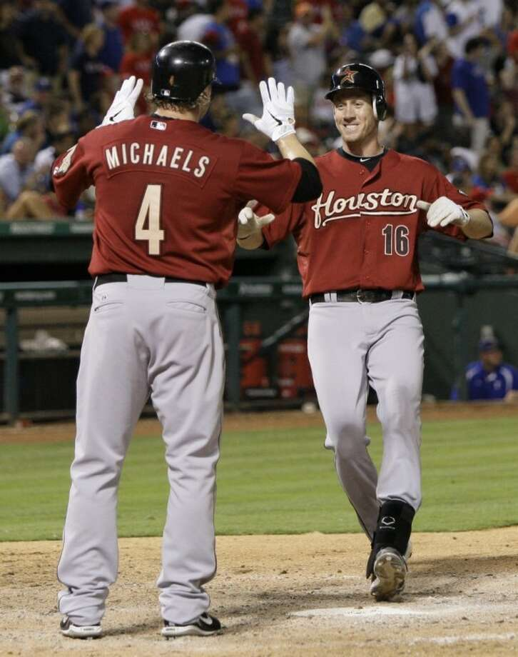 The Houston Astros' Jason Michaels congratulates teammate Matt Downs, who reaches home following a two-run home run off Texas Rangers closer Neftali Feliz that also scored Michaels in the ninth inning of an interleague game on Wednesday in Arlington. The shot lifted the Astros to a 5-3 win. Photo: Tony Gutierrez