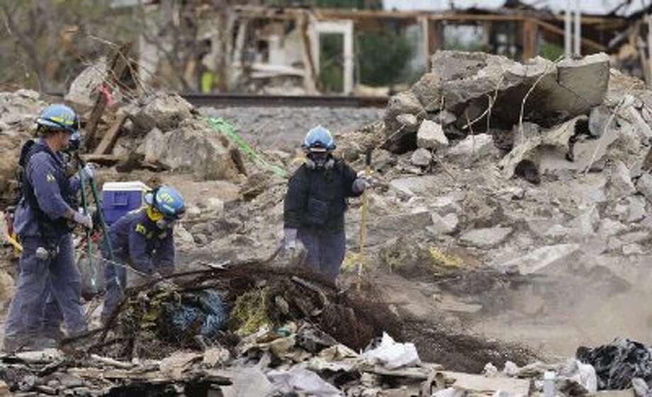 Investigators sift through the debris of the destroyed fertilizer plant in West Thursday. / AP POOL