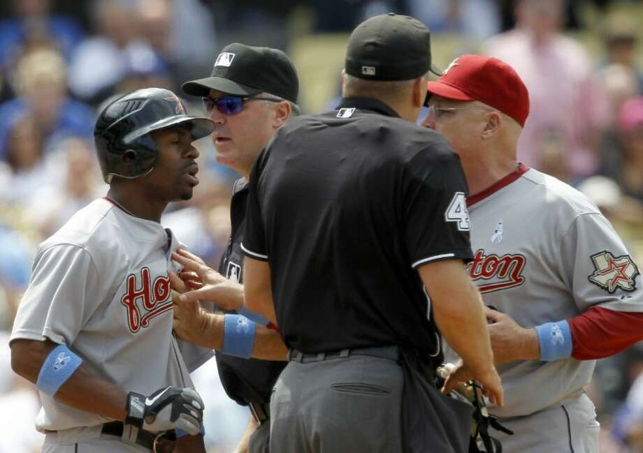 Houston Astros' Michael Bourn, left, is retrained by third base umpire Bill Welke, second from left, and manager Brad Mills, right, from going toward home plate umpire Jeff Nelson, second from right, after Nelson ejected Bourn after striking out during the fifth inning against the Los Angeles Dodgers in Los Angeles, Sunday. Photo: Alex Gallardo