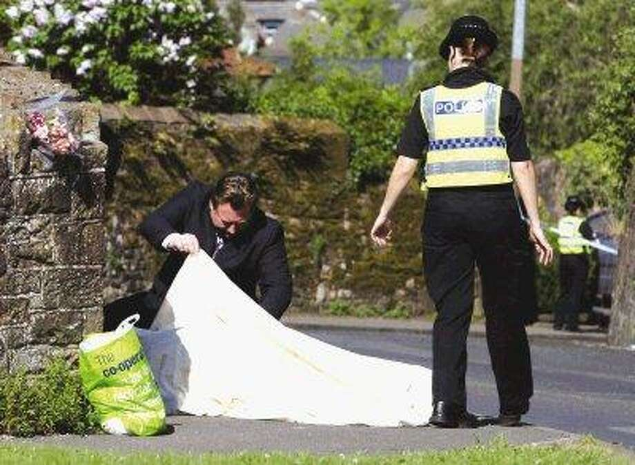 Police look under a sheet covering a body on Hagget End Road, in Egremont northwest England where a person was shot dead when taxi driver Derrick Bird went on a shooting rampage in northwest England Wednesday. British police Bird went on a shooting spree across rural northwestern England, killing and wounding a number of people before turning the gun on himself. The rampage in the county of Cumbria is Britain's deadliest mass shooting since 1996 and shocked a country where gun ownership is tightly restricted. / AP2010