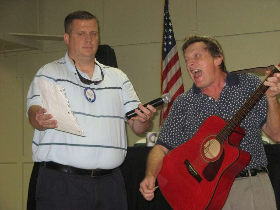 The Conroe Noon Lions Club were entertained recently by comedian Chuck Montgomery, right. Part of the act included a sing-a-long with club member Lion Warner Phelps, left, to the favorite 'Run-a-round Sue.'