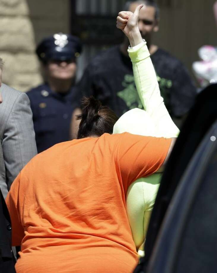 Gina DeJesus gives a thumbs-up as she is escorted toward her home Wednesday, in Cleveland. Photo: Tony Dejak