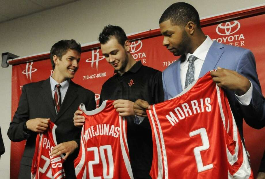 From left, Houston Rockets draft picks Florida center Chandler Parsons, Montenegro forward Donatas Motiejunas and Kansas forward Marcus Morris receive their new jerseys during a news conference Friday in Houston. Photo: Pat Sullivan