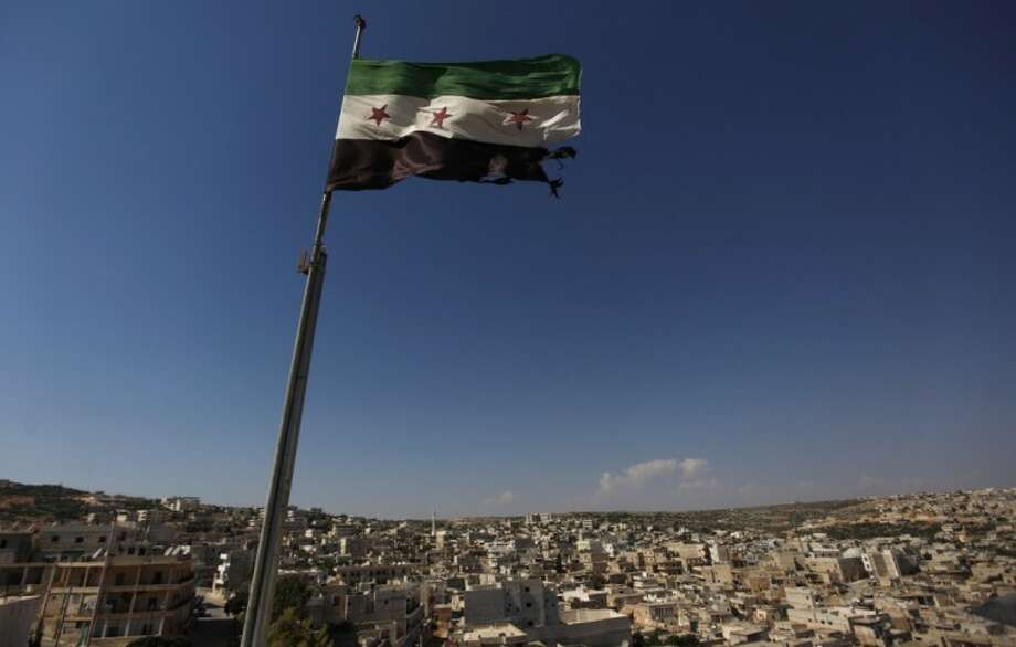 A Syrian revolutionary flag waves on top of a building on the outskirts of Aleppo, Syria, Tuesday. Syrian forces pelted the eastern city of Deir el-Zour with mortars as anti-government protesters were dispersing before dawn Tuesday, killing several people, activists said. Photo: Anonymous