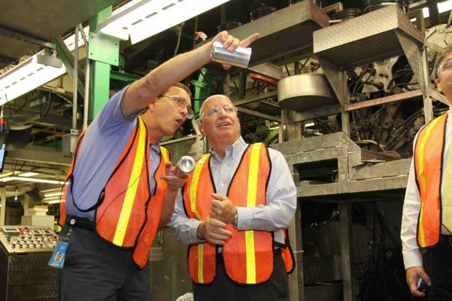 Ellis Freeman with the Ball Corporation shows U.S. Rep. Kevin Brady, R-The Woodlands, the process the company uses to make aluminum cans during a tour of the company's facility in Conroe Thursday.