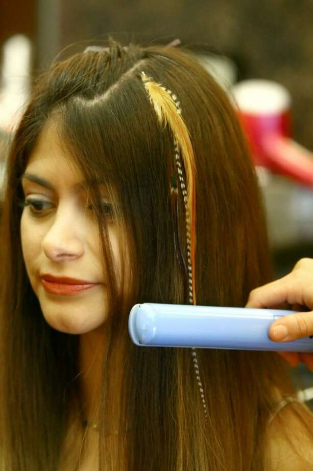 Feather hair extensions are installed at SOZO Hair Design in Tomball. Photo: Staff Photo By Karl Anderson