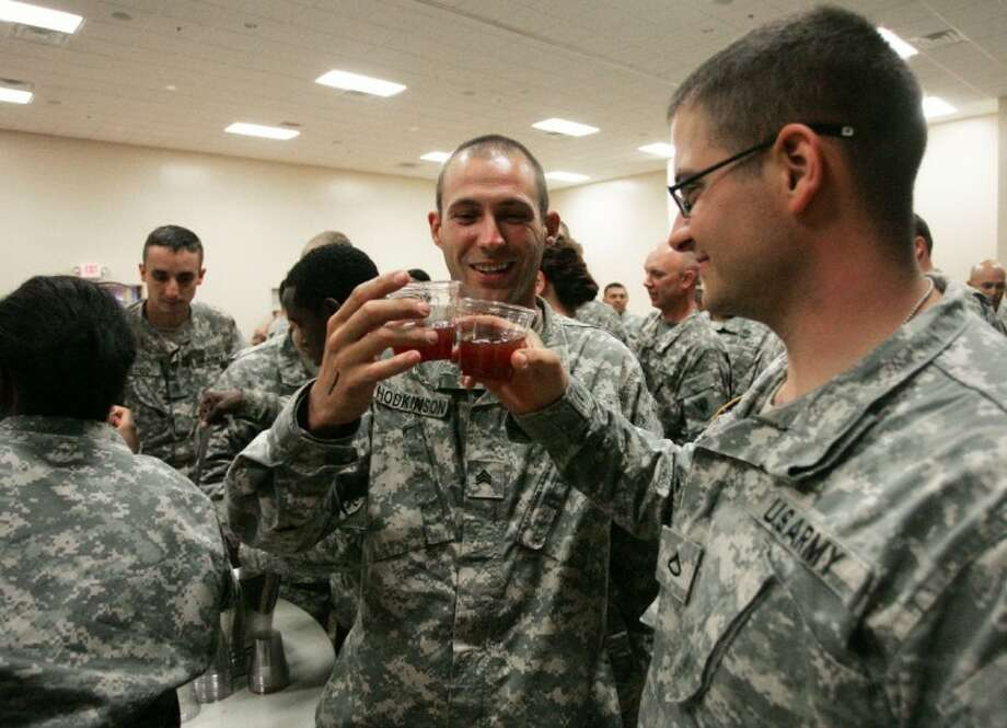 Sgt. Ryan Hodkinson, left, and Pfc. John Allen share a toast as they drink some of the grog during a ceremony held Saturday at the North Montgomery County Community Center in Willis.