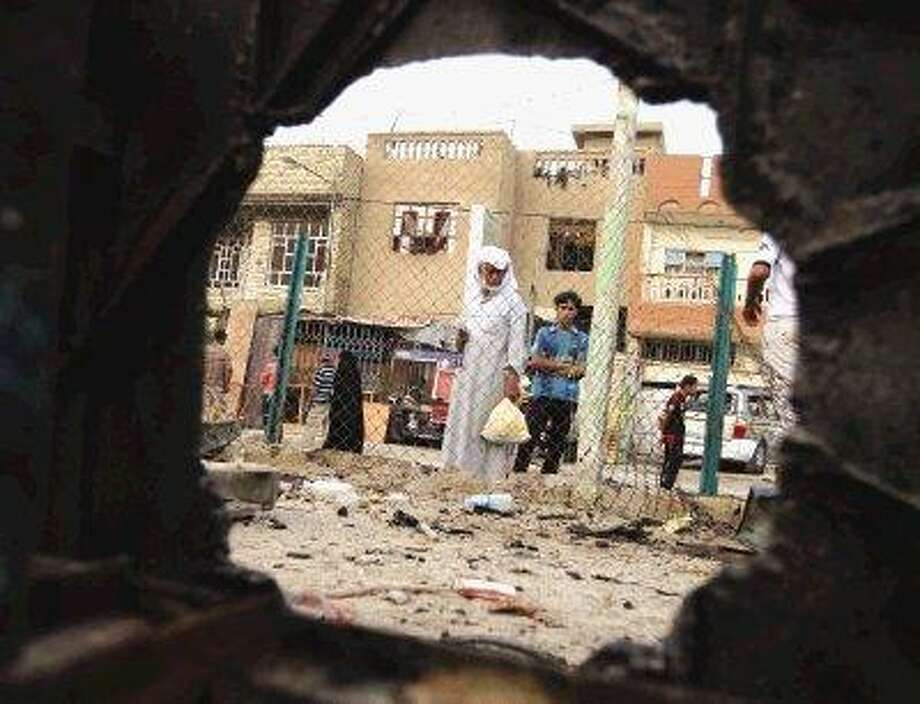 Iraqi People, seen through a shrapnel hole, inspect the site of a car bomb attack in Baghdad, Iraq, Thursday. A car bomb ripped through a popular cafe on Wednesday evening, killing nine young people. / AP2010