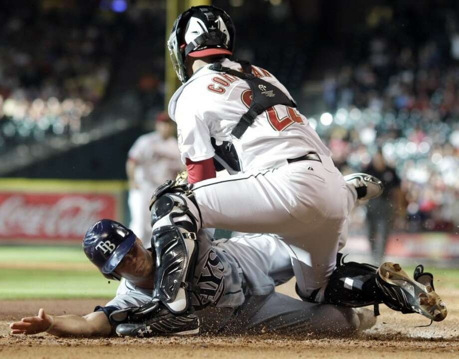 Tampa Bay Rays' Reid Brignac, left, slides safely into home plate to score as Houston Astros catcher Carlos Corporan tags him during the second inning Saturday in Houston.