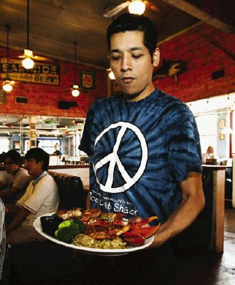 Marco, a server at Joe's Crab Shack, shows off the colorful uniform shirt worn by restaurant staff as he delivers a platter of seafood during a recent visit to the eatery.