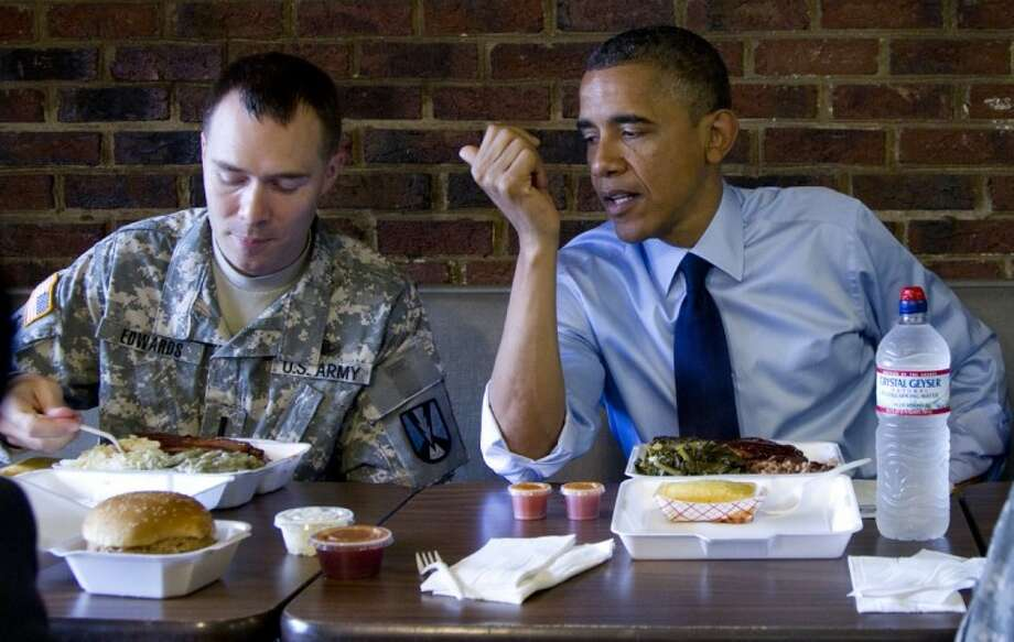 President Barack Obama and Army First Lt. William Edwards, a 2012 Military Fatherhood Award Winner, eat lunch Wednesday during a visit to Kenny's BBQ restaurant in Washington. Photo: Carolyn Kaster