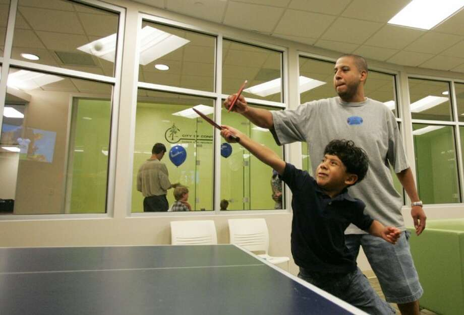 Alberto Fierros plays ping-pong with his son Alejandro Lopez-Fierros, 5, on the opening day Saturday of the C.K. Ray Recreation Center in Conroe.