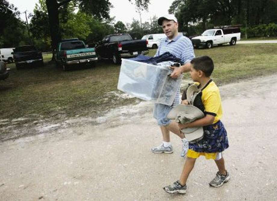 Collin Curry, 7, helps fellow volunteer Dan Shaw carry donated clothing for displaced Grimes County residents Wednesday to the Plantersville Town Hall.