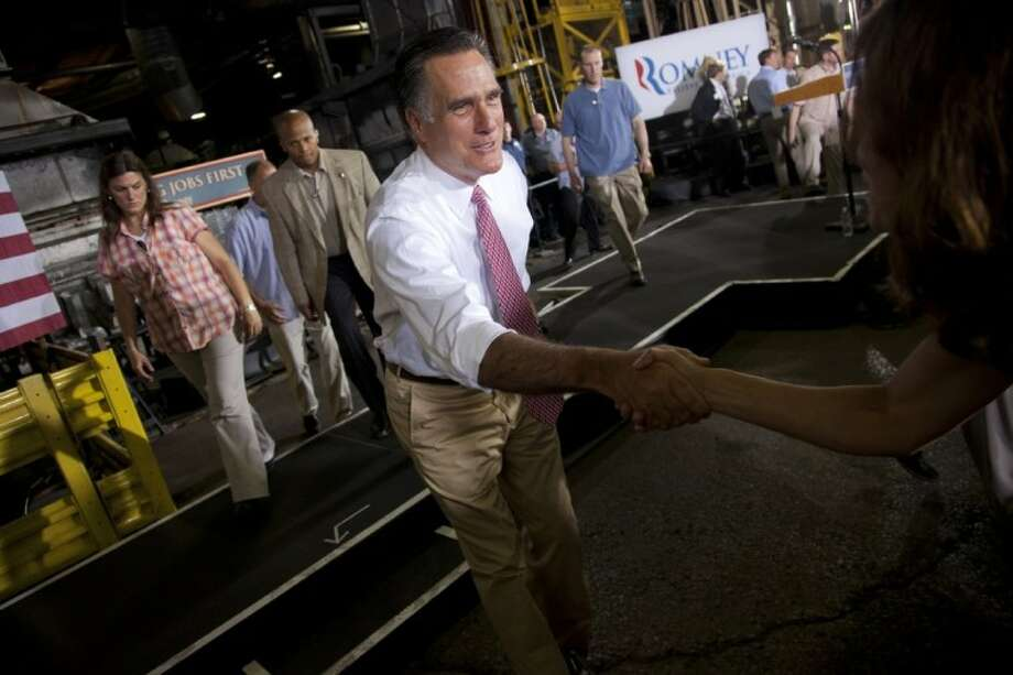 Republican presidential candidate and former Massachusetts Gov. Mitt Romney shakes hands during a campaign stop at Seilkop Industries in Cincinnati, Ohio, Thursday. Photo: Evan Vucci