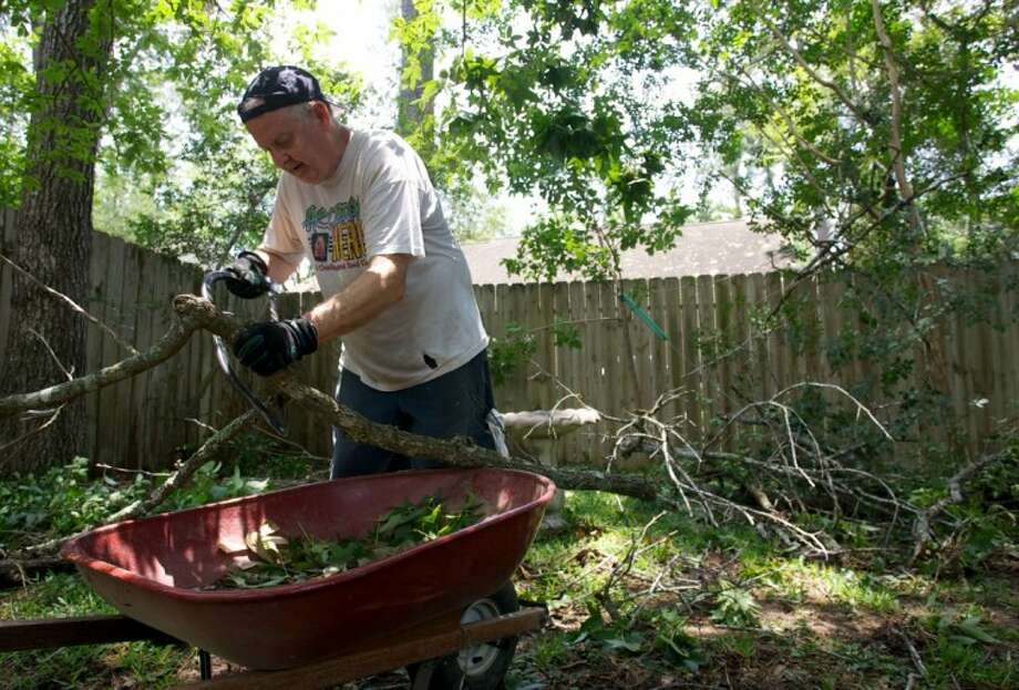 The Woodlands resident Gene Mathews cuts branches into smaller pieces to fit in his wheelbarrow as he works on removing tree debris left in his back yard after strong storms hit Montgomery County June 12. Mathews' home in the Village of Indian Springs was hit by a large tree, which required a crane to remove.