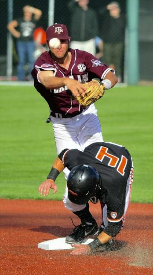 Texas A&M 's Mikey Reynolds throws to first over Oregon State's Andy Peterson on Sunday night. Oregon State eliminated the Aggies from the NCAA tournament, taking a 6-1 victory. Photo: Greg Wahl-Stephens