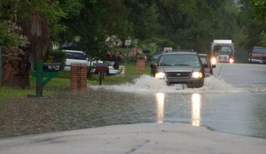 A sport utitlity vehicle attempts to cross high water Friday on River Oaks Drive in Conroe. / The Courier