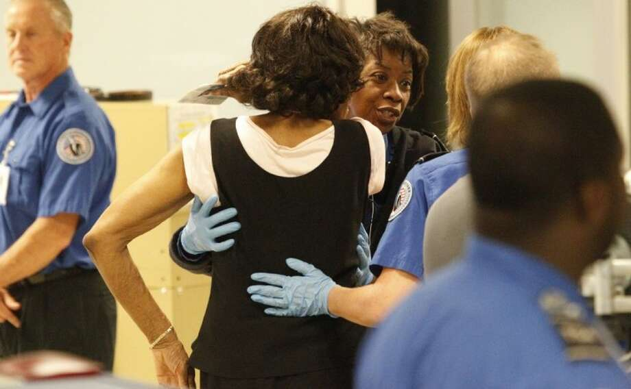 In this photo taken June 22, TSA inspectors check a passenger at a checkpoint at Dallas-Fort Worth International airport in Grapevine. Photo: LM Otero