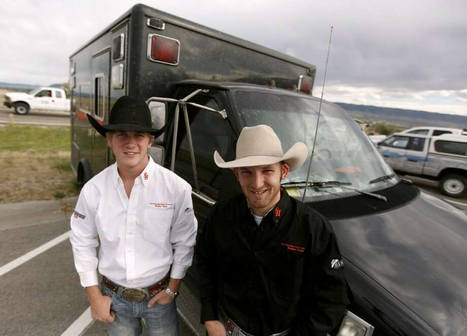 Sam Houston State University rodeo teammates Sterling Crawley, from Stephenville, and Jeremy Melancon, from Buffalo, Texas, pose in front of their converted 1993 ambulance in the parking lot of the Casper Events Center before the start of Tuesday night's performance of the CNFR.