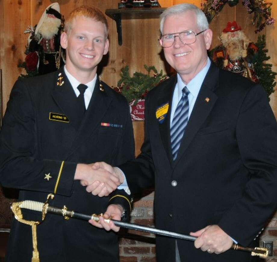 U.S. Navy Capt. Mike Coats (Ret.) presents Ensign Travis Keating, left, with the Smith-McCool Memorial Sword Jan. 4 at the Taste of Texas Restaurant in Houston. The sword is presented annually to U.S. Naval Academy graduates from the Texas Gulf Coast with the highest standing in their class.