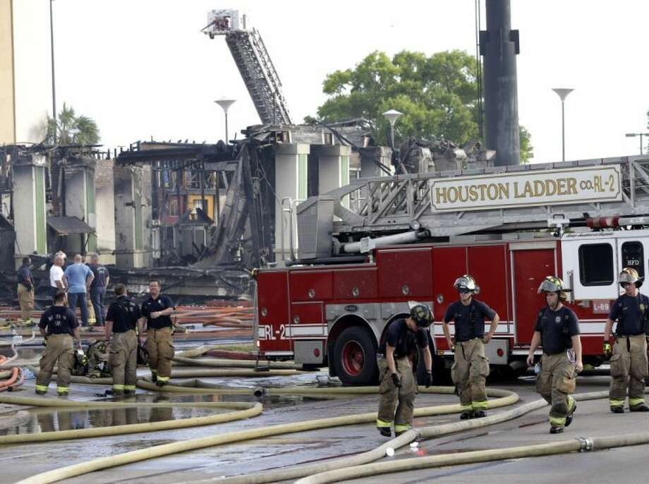 Houston firefighters clean up the scene where four firefighters were killed while battling a fire that engulfed a motel and restaurant on Friday in Houston. Photo: David J. Phillip