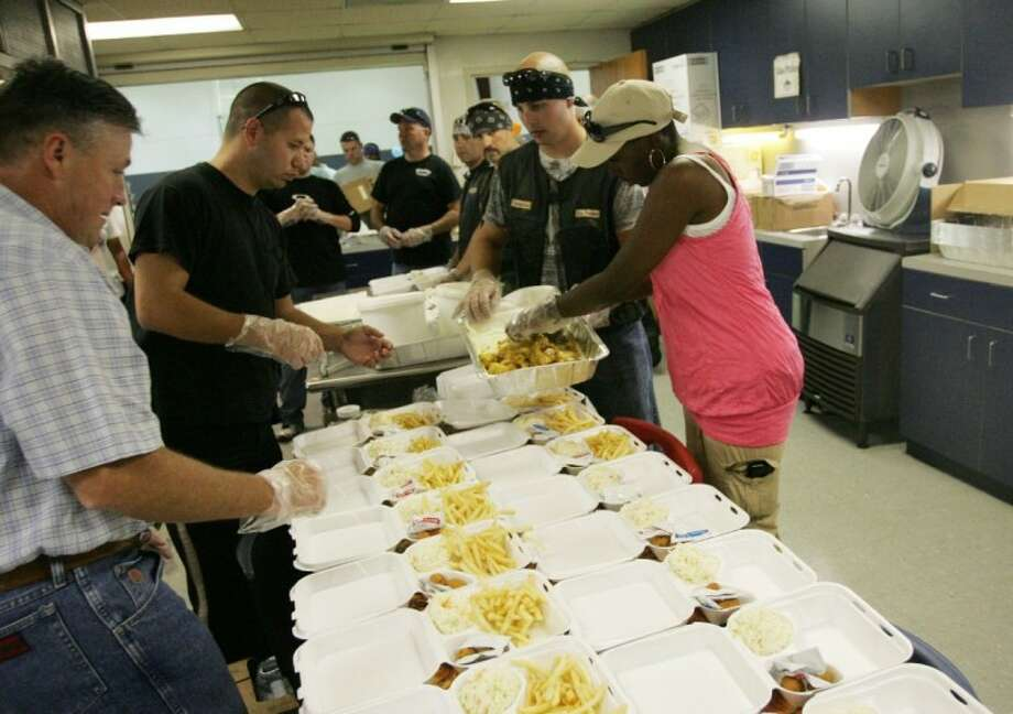 Volunteers prepare fish-fry meals during a benefit for Harris County Precinct 4 Constable's deputy Cpl. Eric Davis Wednesday at the Cypress Creek Christian Church and Community Center in Spring. Davis was seriously injured in a motorcycle accident in early June.