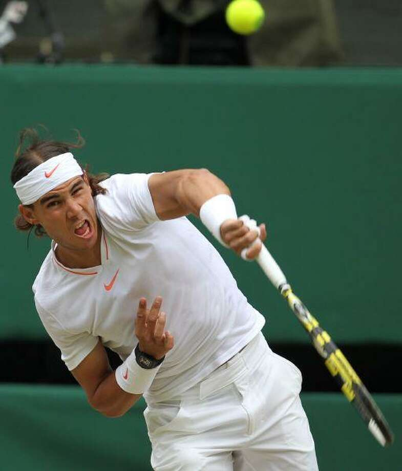 Rafael Nadal serves to Andy Murray during their men's singles semifinal on the Centre Court at the All England Lawn Tennis Championships at Wimbledon Friday. / AP