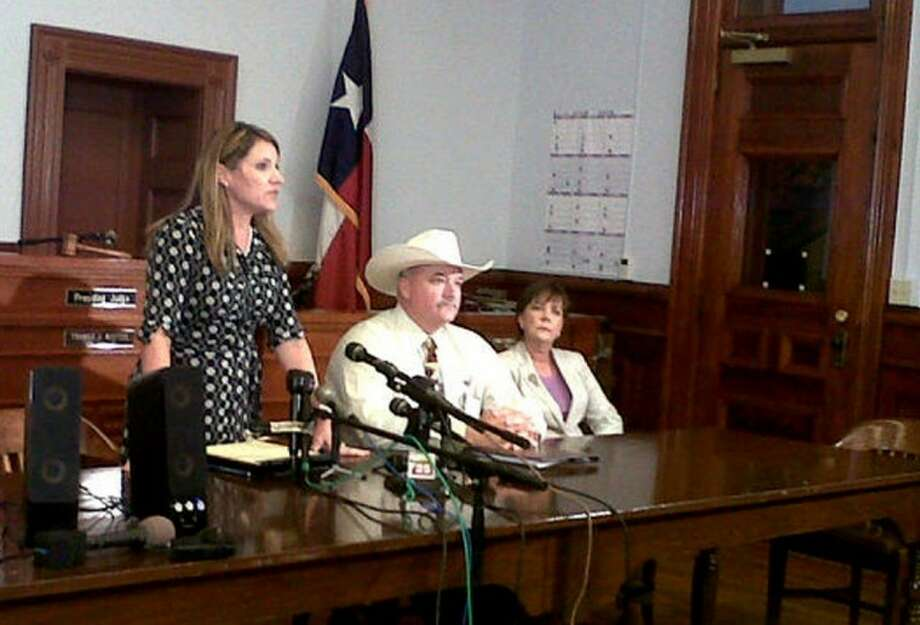 Heather McMinn, district attorney for Guadalupe, Gonzales and Lavaca counties, speaks Tuesday at a news conference in Hallettsville with Lavaca County Sheriff Micah Harmon, second from right, and V'anne Huger, right, attorney for the father, at a news conference on a Texas father who beat to death a man who tried molesting his 5-year-old daughter. Officials said the Lavaca County grand jury met Tuesday and declined to return an indictment against the father in the death of 47-year-old Jesus Mora Flores. Photo: Ramit Masti