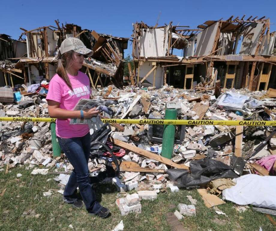 Texas A&M University freshman Heather Warfield collects baseball cards Saturday from a nearby apartment complex in West that was damaged due to the explosion at a fertilizer plant April 17. More than 124 students donated their time to help clean up parts of West devastated by the explosion. Photo: Rod Aydelotte