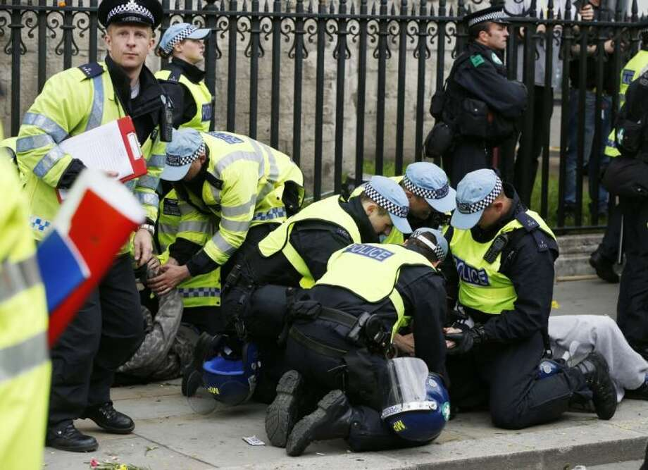 British police officers arrest anti-fascist demonstrators protesting against members of the British National Party (BNP), not seen, during a demonstration in central London, Saturday. BNP supporters gathered to protest the May 22 killing of British soldier Lee Rigby. Photo: Lefteris Pitarakis