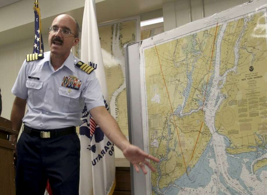 Deputy Commander of Coast Guard Sector New York Capt. Gregory Hitchen gestures towards a map of New York Harbor while speaking at a news conference in New York Wednesday. Similarities in a caller's voice and phrasings have led the Coast Guard to believe there's a link between a hoax distress call reporting a yacht explosion off New Jersey and a mayday call in Texas last month. Photo: Seth Wenig