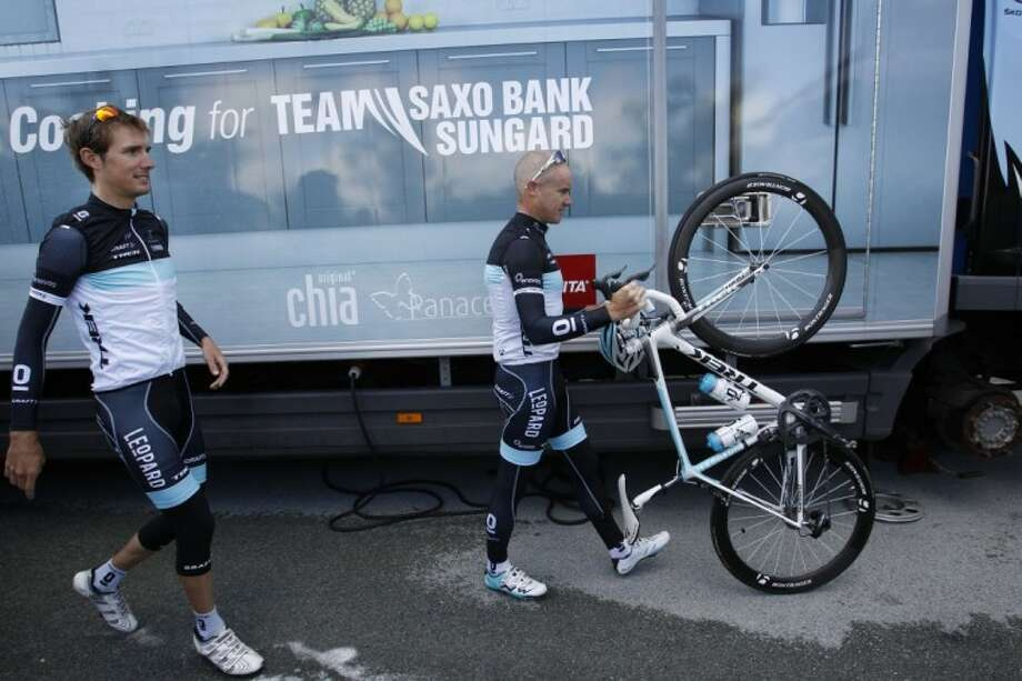 Andy Schleck, left, and Stuart O'Grady, of the Leopard Trek team, pass the Saxo Bank-Sungard team bus prior to leaving for a training ride near Les Herbiers, western France, on Thursday. The Tour de France starts on Saturday with the first stage of 119 miles starting in Passage du Gois and finishing in Mont des Alouettes, Les Herbiers.