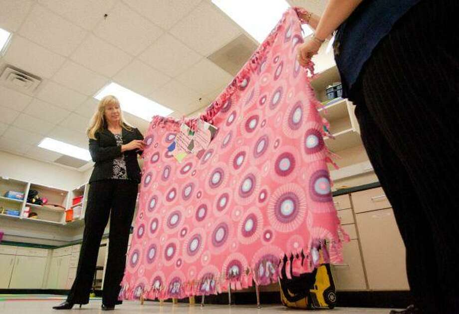 """Elizabeth Jones, Montgomery County Women's Center development director, examines a blanket made by life skills students at C.C. Hardy Elementary in Willis. Students took part in """"Project Warm Heart"""" and made blankets for the MCWC, which they presented during a spaghetti lunch Tuesday at the school."""