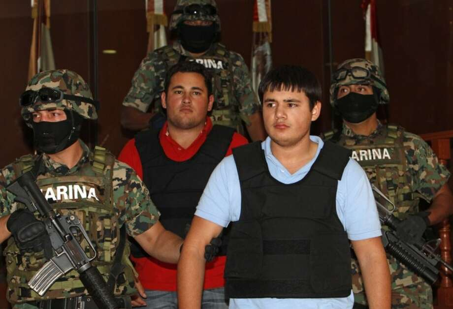 "Mexican marines escort Jesus Alfredo Guzman Salazar, 26, in red T-shirt, and Kevin Beltran Rios, during their presentation to the media in Mexico City, Thursday. Mexican marines detained Salazar who is allegedly one of the sons of Mexico's most-wanted drug kingpin, Joaquin ""El Chapo"" Guzman Loera, leader of the powerful Sinaloa cartel. Photo: Eduardo Verdugo"