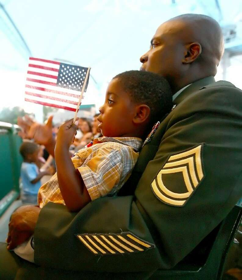 Retired Army Sgt. 1st Class Timothy Maddox and his grandson, Adonis, watch the Houston Symphony's Star-Spangled Salute Sunday at the Cynthia Woods Mitchell Pavilion. Photo: Staff Photo By Karl Anderson