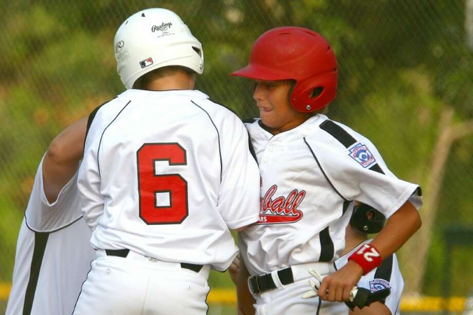 Tomball's Cameron Faulkner and Dylan Simpson celebrate their runs Friday at the ORWALL Sports Complex in Spring.