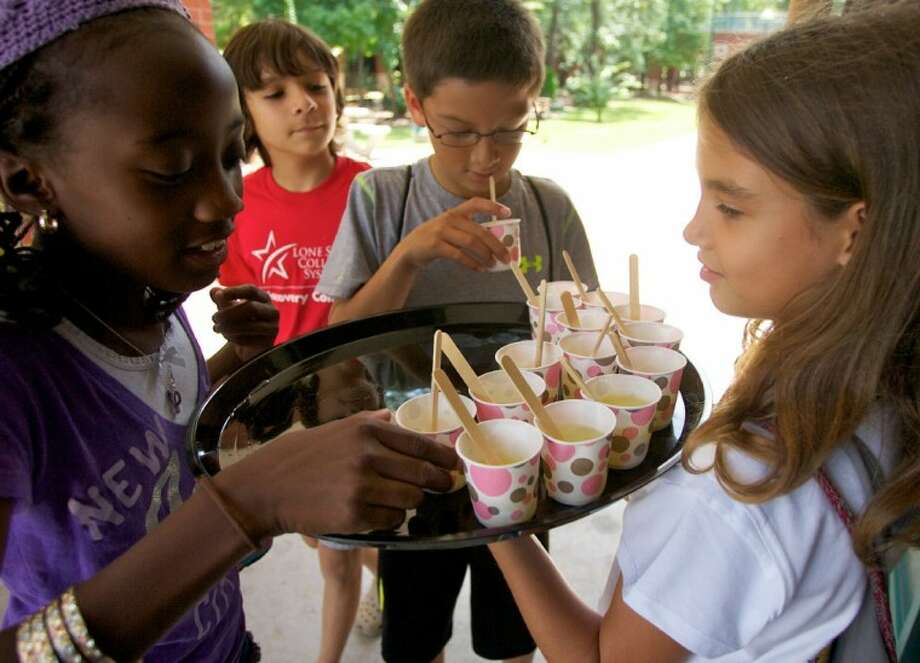 Lulu Whitson, 9, hands out lemonade at Thursday's Discovery College Youth Camp lemonade stand at Lone Star College-Montgomery.