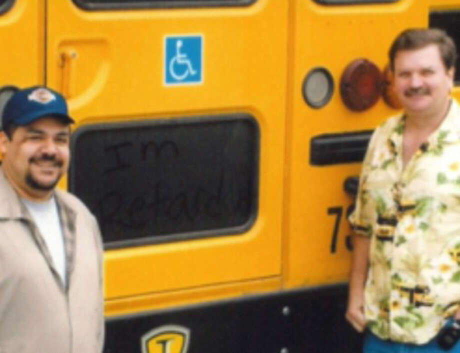 """Joe Dives, transportation director for the Magnolia Independent School District, and Kevin Kreitz, assistant transportation director, stand next to a bus with """"I'm retardid"""" written in the dust on the back of a school bus for special needs students."""