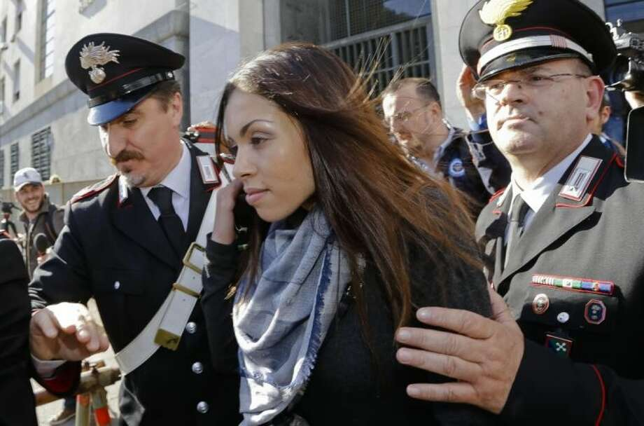 Karima el-Mahroug is escorted outside the Milan's Law court by two Carabinieri police officers after giving her testimony at the trial of three former Berlusconi aides accused with procuring her and other woman for prostitution, in Milan, Italy, Friday. Photo: Luca Bruno