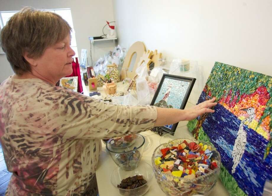 Mosaic Mesa owner Karen McClinch shows a piece created by mosaic at her store in Old Town Spring. Photo: Staff Photo By Eric Swist