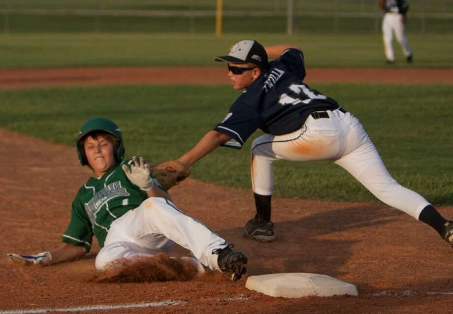 ORWALL National's Zachary Twilla tags out ORWALL American's Kevin Skweres as he makes a slide for third during Thursday night's game in Spring. National won, forcing an elimination game today. Visit www.yourconroenews.com for more on Thursday's game.