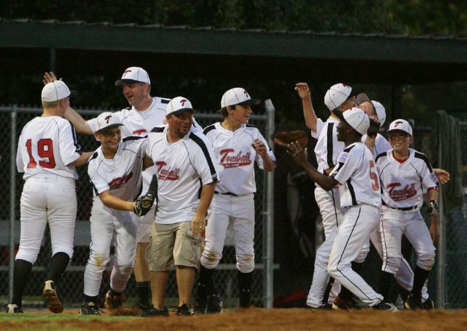 Tomball All-Star players and coaches celebrate their 8-3 win over ORWALL American in the championship game of the Little League Texas District 28 Majors tournament on Wednesday night at the ORWALL Sports Complex in Spring.