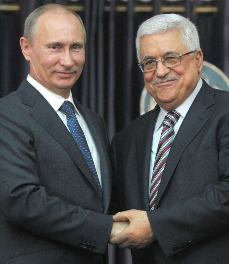 Russian President Vladimir Putin, left, and Palestinian President Mahmoud Abbas, right, shake hands during a media briefing in the West Bank town of Bethlehem, Tuesday. Photo: Alexei Druzhinin