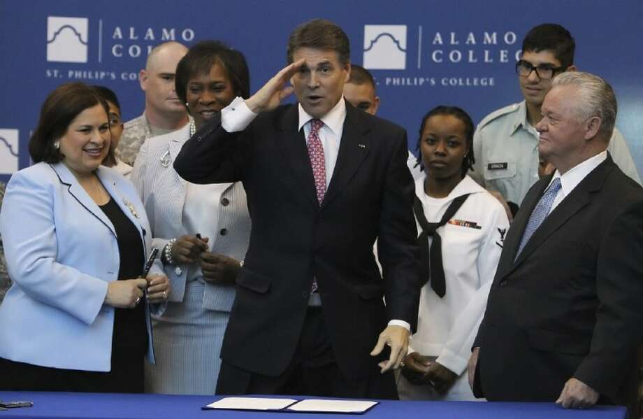 Gov. Rick Perry, joined by State Senator Leticia Van De Putte, from left, St. Philip's College President Adena Williams Loston, Texas Workforce Commissioner Ronny Congleton, far right, and members of the military, signs a bill to help military veterans gain college credit for their service Thursday at St. Philip's College in San Antonio. Photo: Kin Man Hui