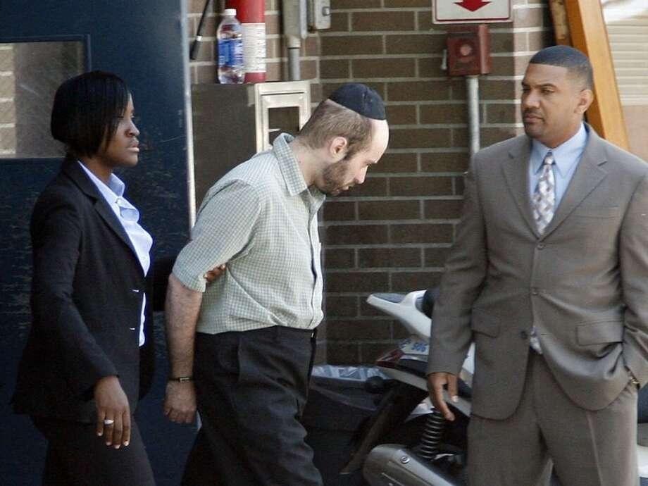 Detectives walk Levi Aron, center, to a police car at the Brooklyn borough of New York's 67th precinct on Thursday. Photo: DAVID KARP