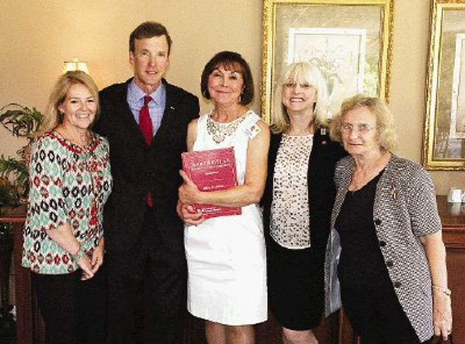 """From left, Becky Ball, Dr. Jeffrey Addicott, current MCRW president Mary Lea Kirk, Merrillyn Kulis and Lilija Grumulaitis pose for a picture at Thursday's luncheon. Kirk is holding a copy of Addicott's book, """"Terrorism Law."""""""